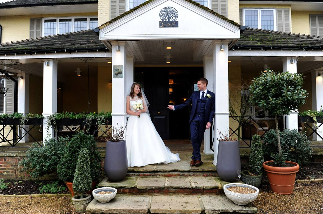 Groom captured in this wedding photo beckoning to his bride to join him as they stand in front of Russets Country House at the lovely wedding venue in Surrey
