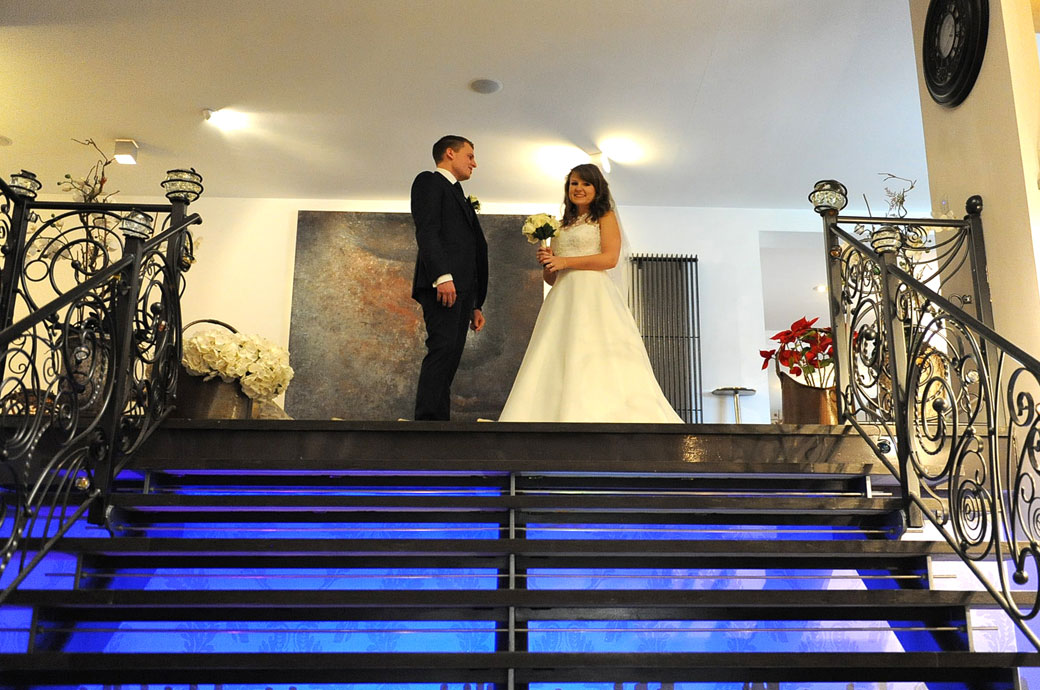 Wedding picture of a happy smiling Bride standing at the top of the blue up lit staircase with her husband at the delightful wedding venue Russets Country House in Surrey