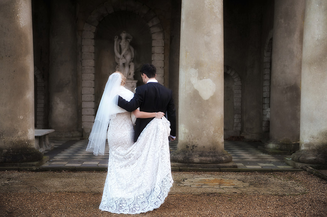Couple captured in this wedding photograph from Wotton House in Dorking Surrey walking arm in arm over to the fabulous Roman Temple
