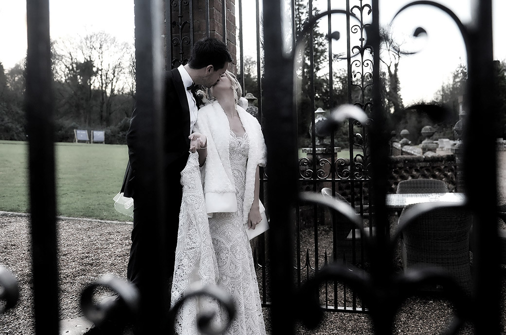 Dramatic and romantic newlywed's kiss captured through the gate railings leading from the garden terrace at Surrey wedding venue Wotton House