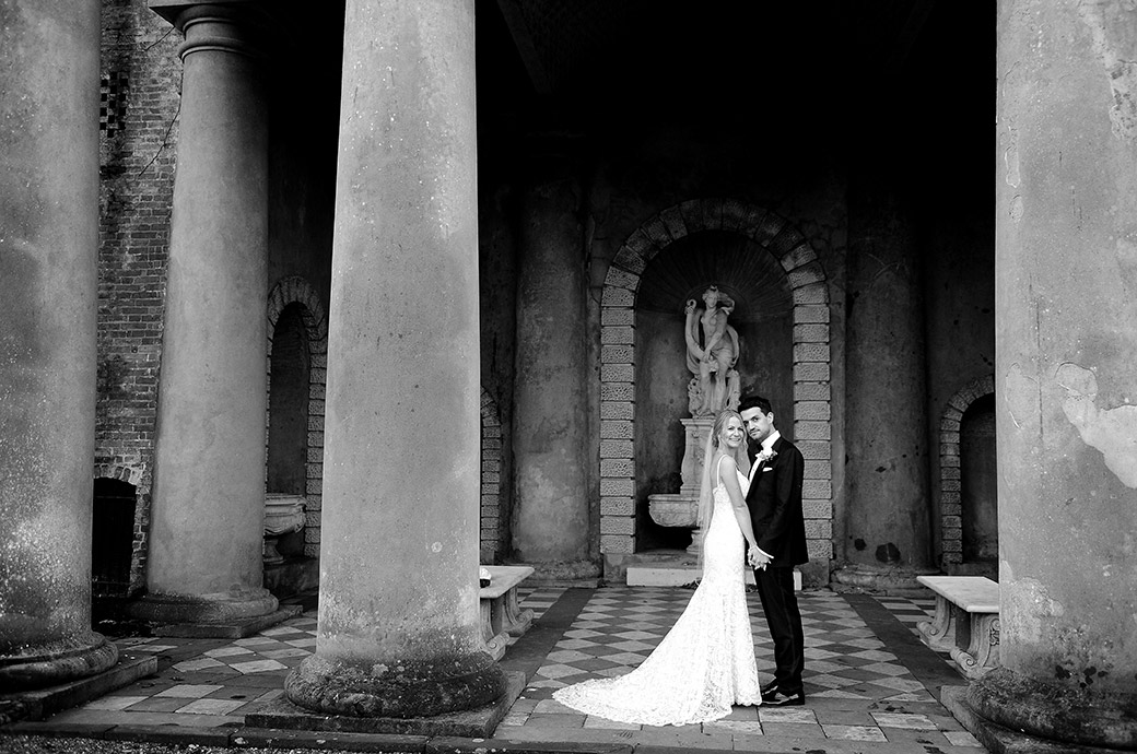 Handsome newlyweds standing together next to the mighty columns of the majestic Roman Temple at the award winning wedding venue Wotton House in Dorking Surrey