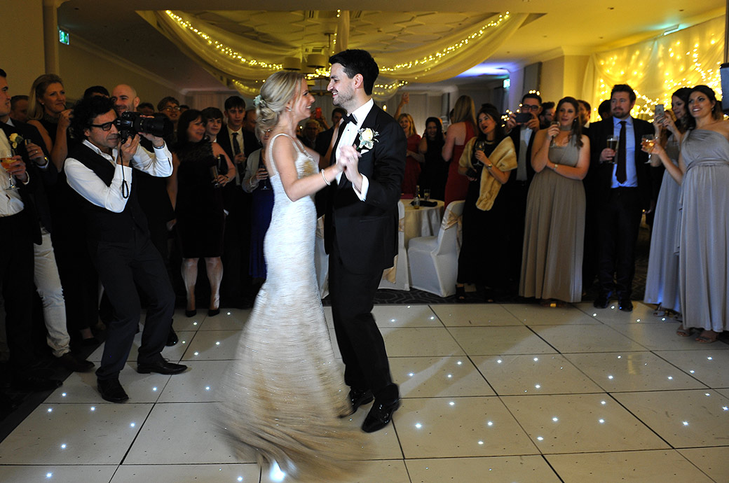 Smiling Bride and Groom captured on the dance floor ff the Evelyn Suite at Wotton House alongside a Surrey Lane wedding photographer