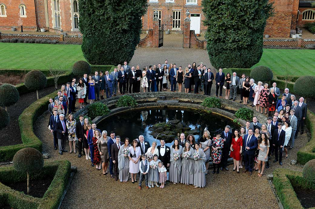 All the wedding guests at Surrey venue Wotton House standing around the ornamental pond and fountain and looking up to the photographer on top of the Roman Temple