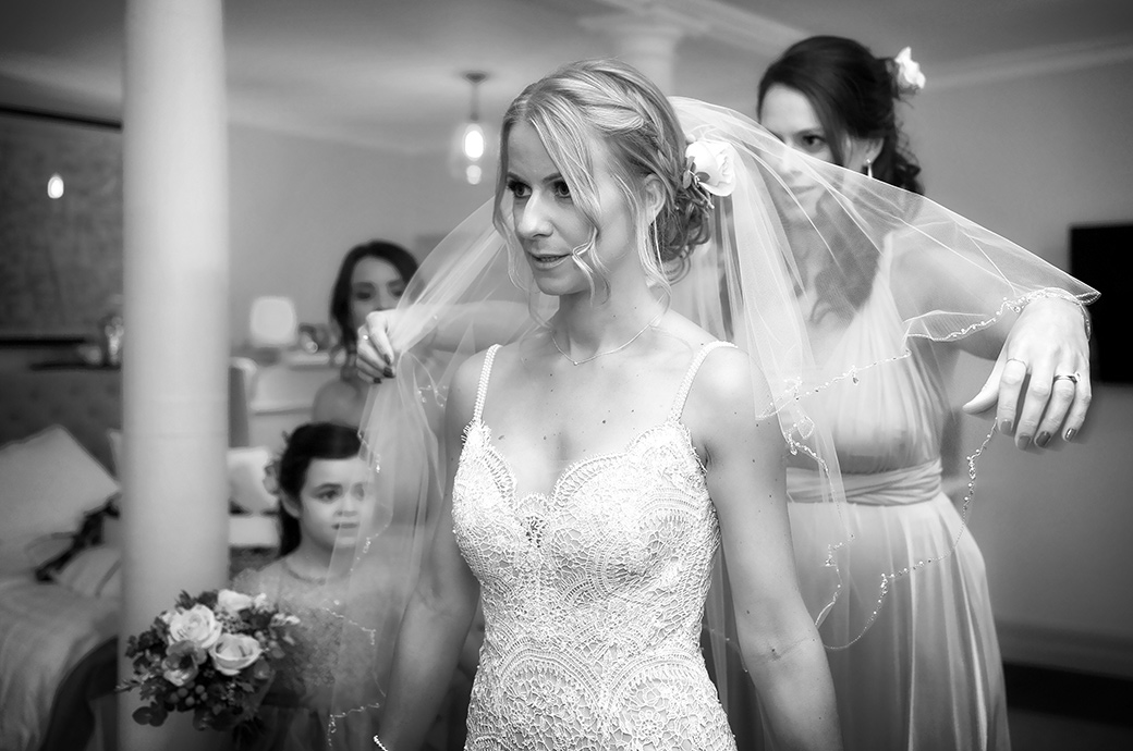 Slightly nervous Bride at Surrey venue Wotton House in Dorking captured as a Bridesmaid helps her with her wedding veil in the Bridal Suite
