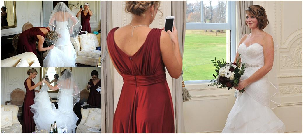 Bridesmaids in the Bridal Suite at Addington Palace in Croydon Surrey taking pictures with their mobiles of the beautiful Bride in her wedding dress ready to leave for The Chapel
