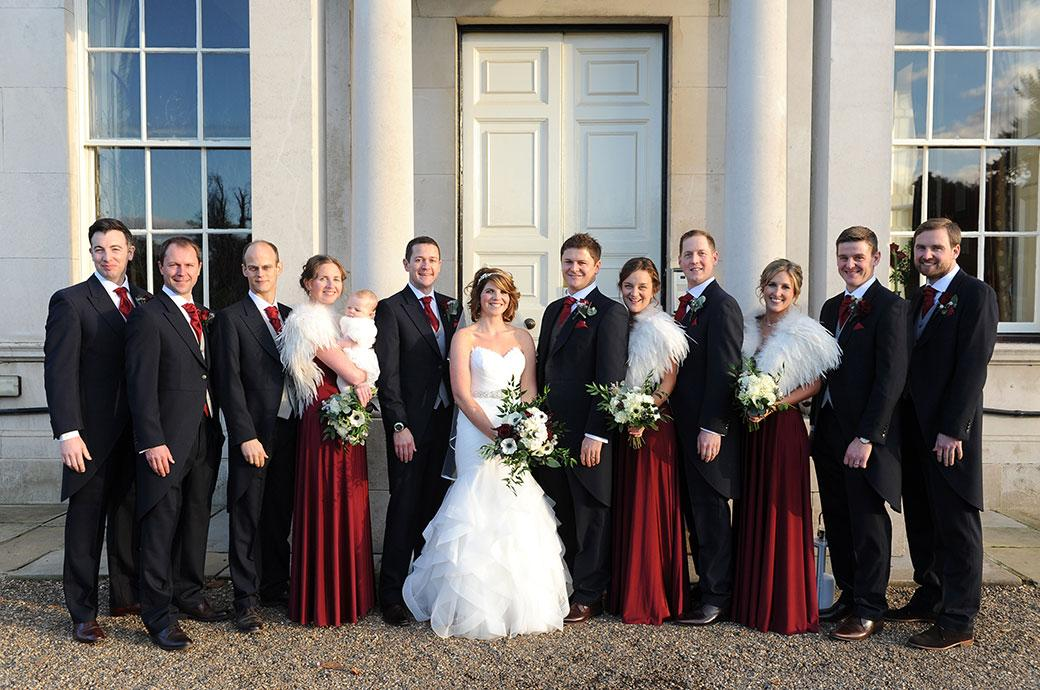 Bride and groom with their Bridesmaids and groomsmen outside the stately front entrance to Surrey wedding venue Addington Palace in this classic group wedding photograph