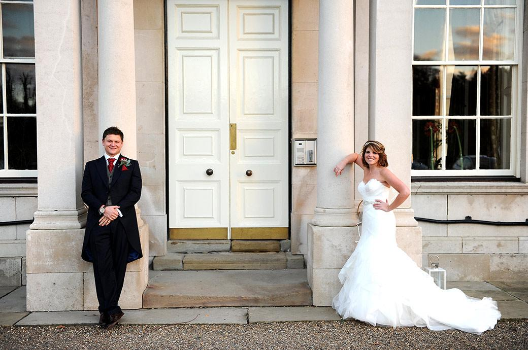 Handsome smiling Bride and Groom take a relaxing pose as they lean up against the large columns of the grand and stately Addington Palace wedding venue in Croydon Surrey