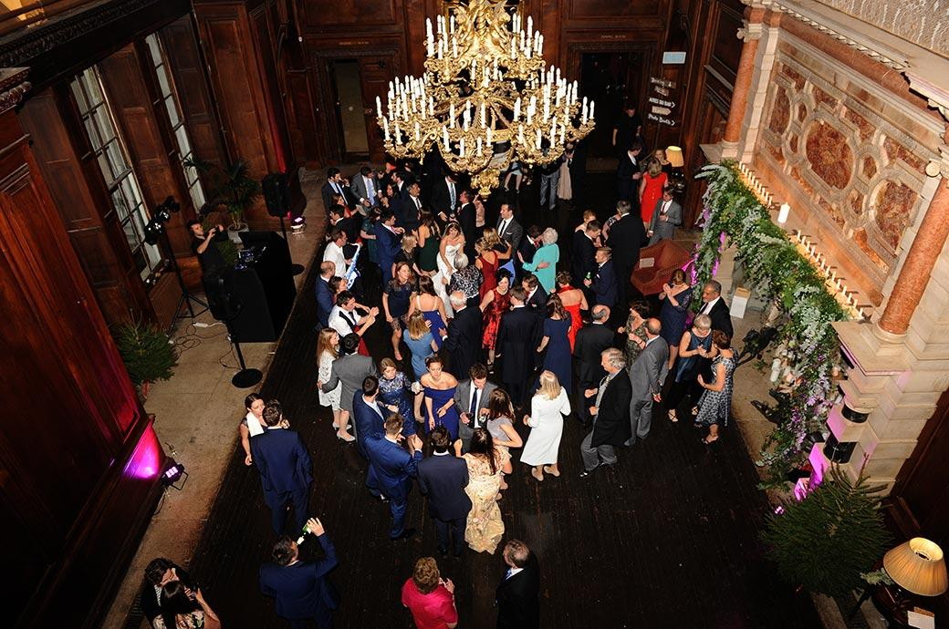 A wedding photograph of everyone dancing in the impressive Great Hall at Surrey wedding venue Addington Palace captured from the first floor balcony