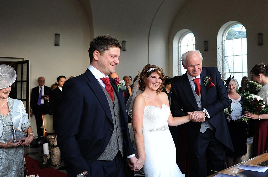 All smiles in the chapel at Surrey wedding venue Addington Palace as the bride holds her father's and the Groom's hands as they stand before the marriage registrar