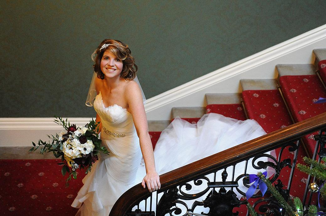 Wedding photograph of a beautiful Bride on the stairs with her bouquet at Addington Palace looking au and smiling to her Surrey Lane wedding photographer