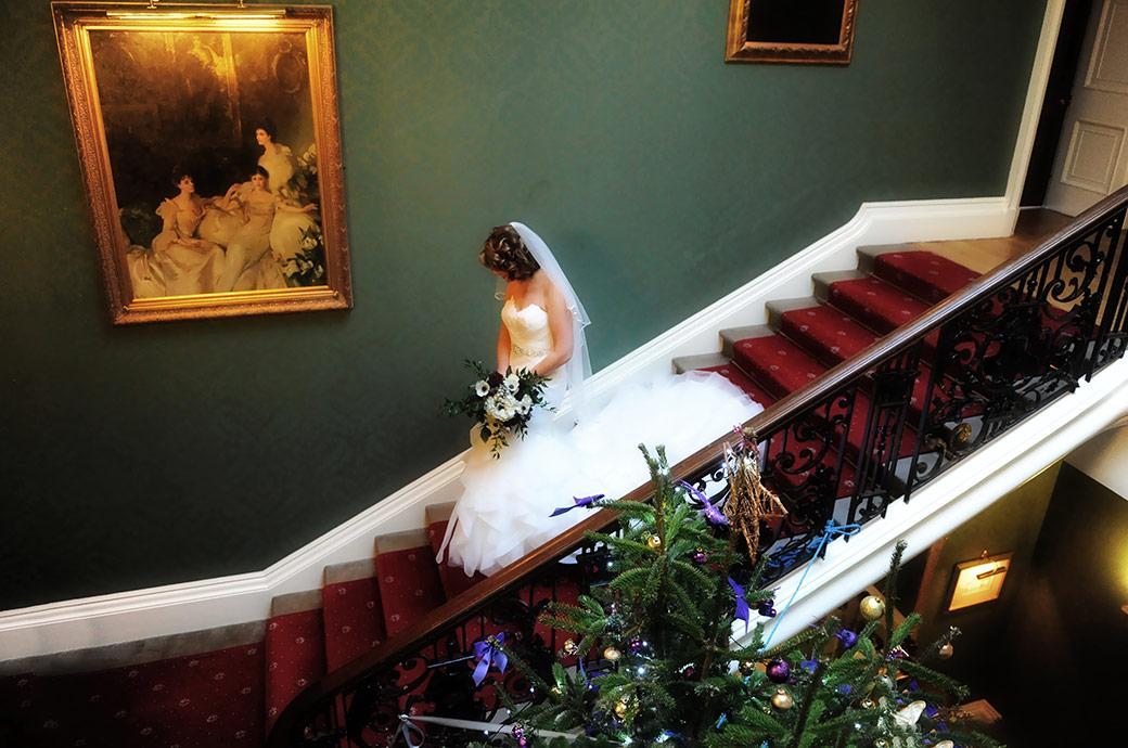 The bride in her stunning dress at the grand and majestic Addington Palace in Surrey walking down the stairs passing a large Christmas tree on route for the chapel for her marriage