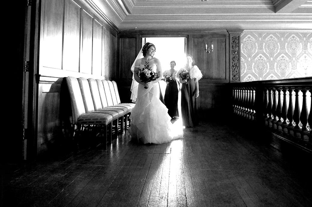 Smiling Bride at Surrey wedding venue Addington Palace caught in the light from the Bridal Suite as she walks along the balcony floor followed by her Bridesmaids