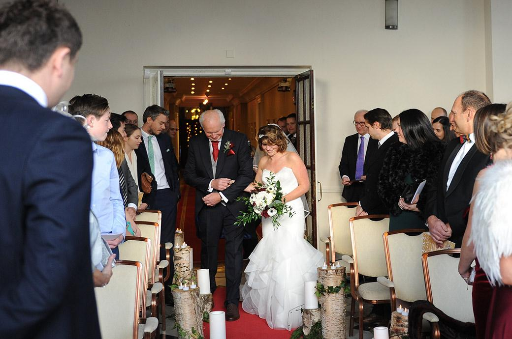 Bride and her father negotiate their way down the narrow aisle of the chapel at the Addington Palace wedding venue in Croydon Surrey which is full of tree branches with candles on top