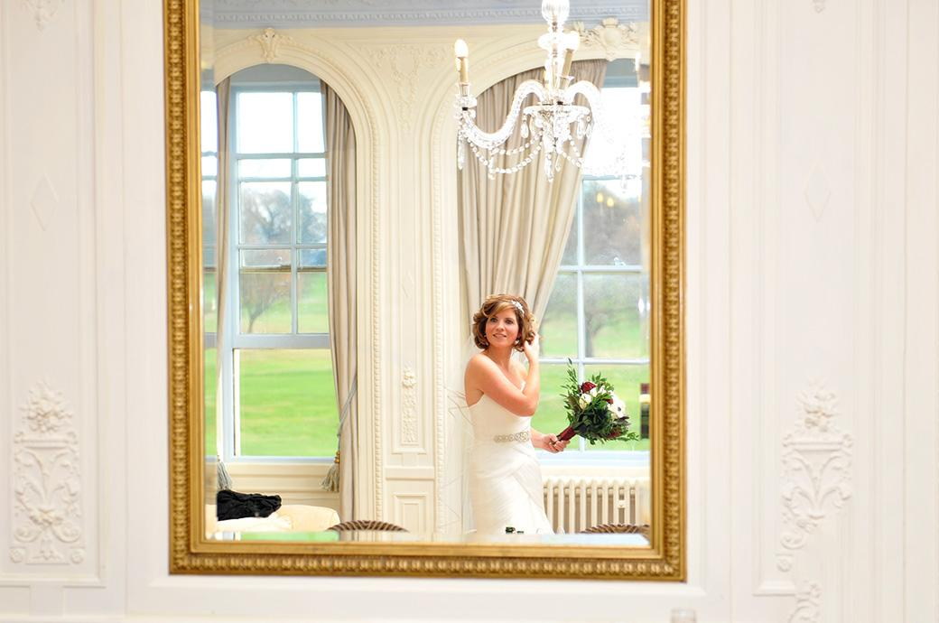 A beautiful bride in the lovely Bridal Suite at Surrey wedding venue Addington Palace in Croydon holding her bouquet as she adjusts her hair in this mirror reflected wedding picture