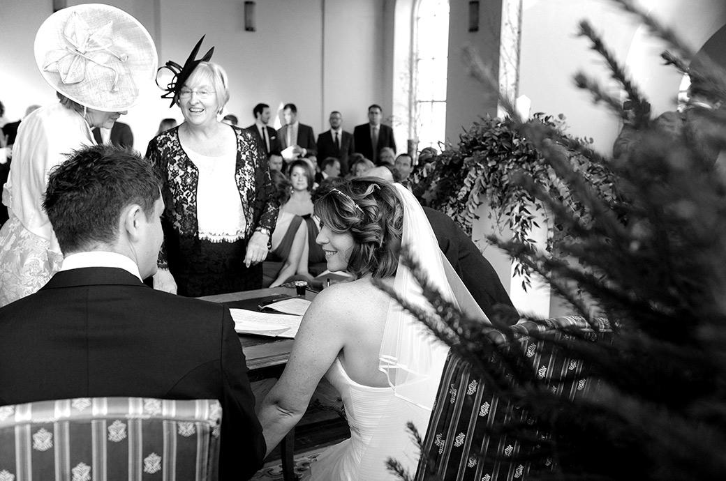 Bride in the chapel at Surrey wedding venue Addington Palace steals a special moment with her Groom as they sit down waiting for their mothers to sign the marriage register