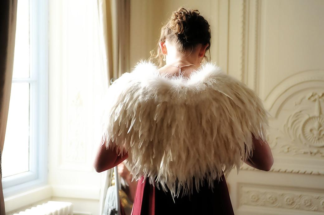 Wedding photo of a Bridesmaid adjusting a necklace wearing an unusual and striking white feather stole in the Bridal Suite at Addington Palace in Croydon Surrey
