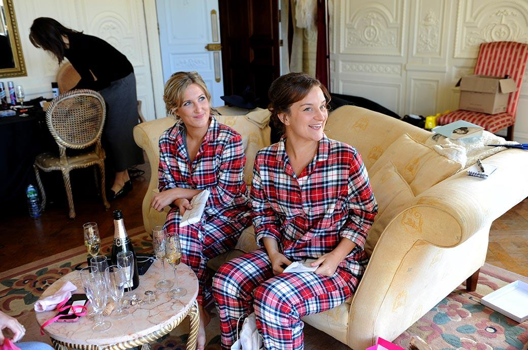 Happy smiling Bridesmaids dressed in tartan pyjamas receiving cards and presents from the Bride on the morning of a wedding at Addington Palace in Croydon Surrey