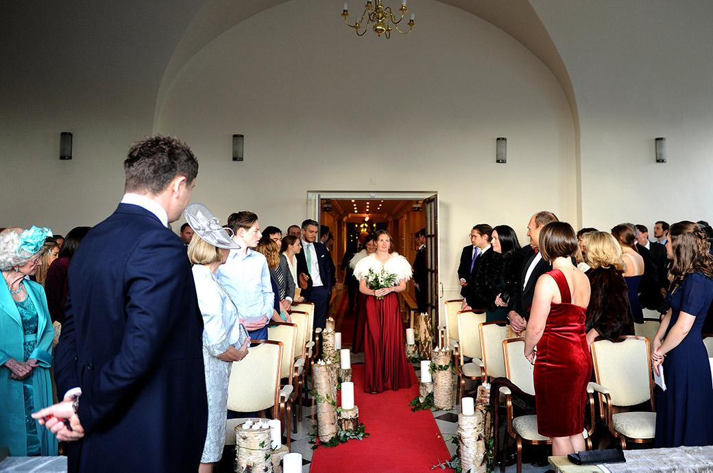 Everyone standing up in the chapel at Surrey wedding venue Addington Palace as the Maid of Honour leads the Bridesmaids down the narrow aisle packed with tree branches and candles