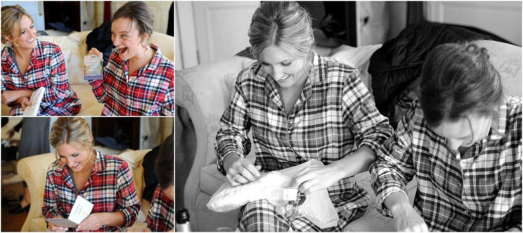 Excited Bridesmaids dressed in tartan pyjamas at Surrey wedding venue Addington Palace smile as they read their cards and open their presents from the Bride