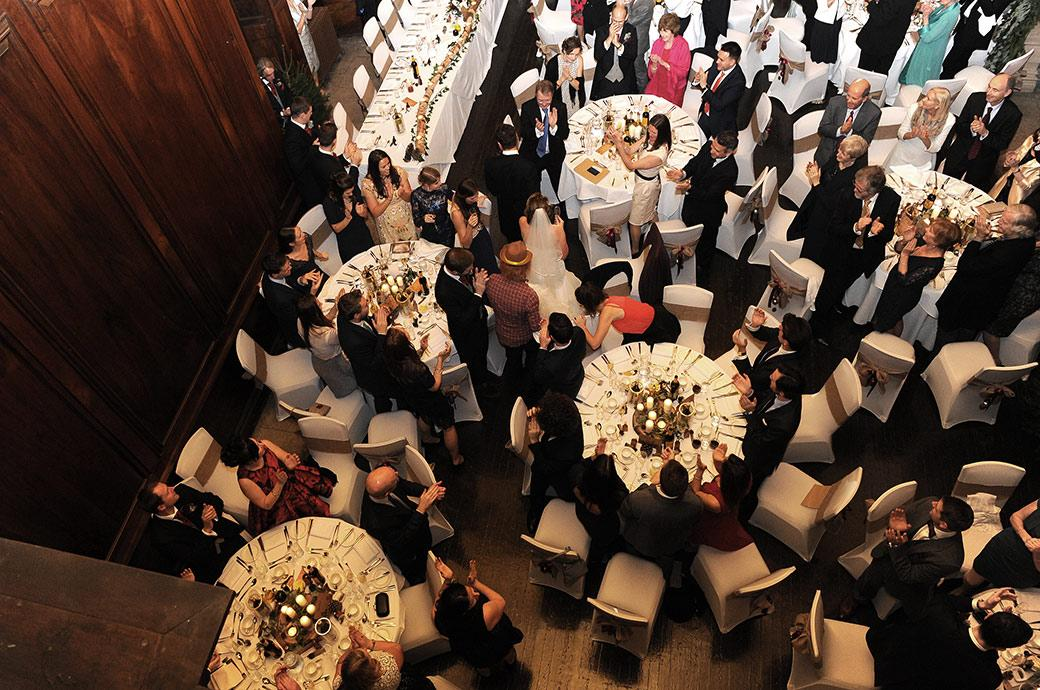 View from above of the Bride and groom at Addington Palace in Surrey wedding venue being applauded as they walk past the guests in the Grand Hall for the wedding breakfast