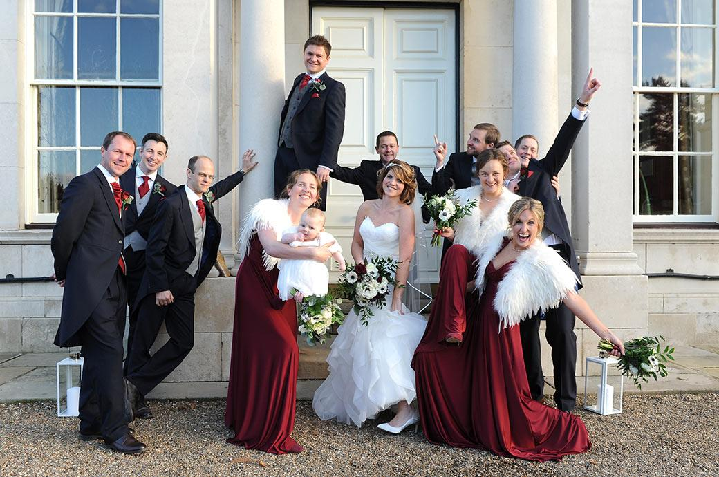 Fun Bride and groom with their Bridesmaids and groomsmen in this group wedding photograph taken at Surrey wedding venue Addington Palace outside the stately front entrance