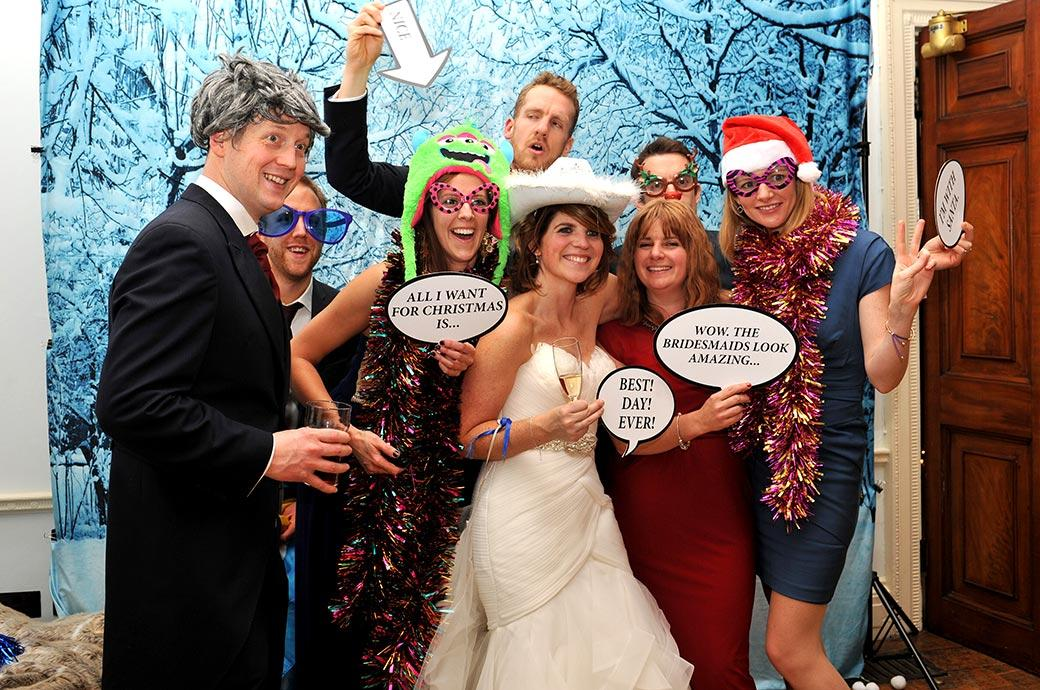 Happy Bride and her guests at Addington Palace in Surrey pose for friends in the open plan ski chalet themed photo booth