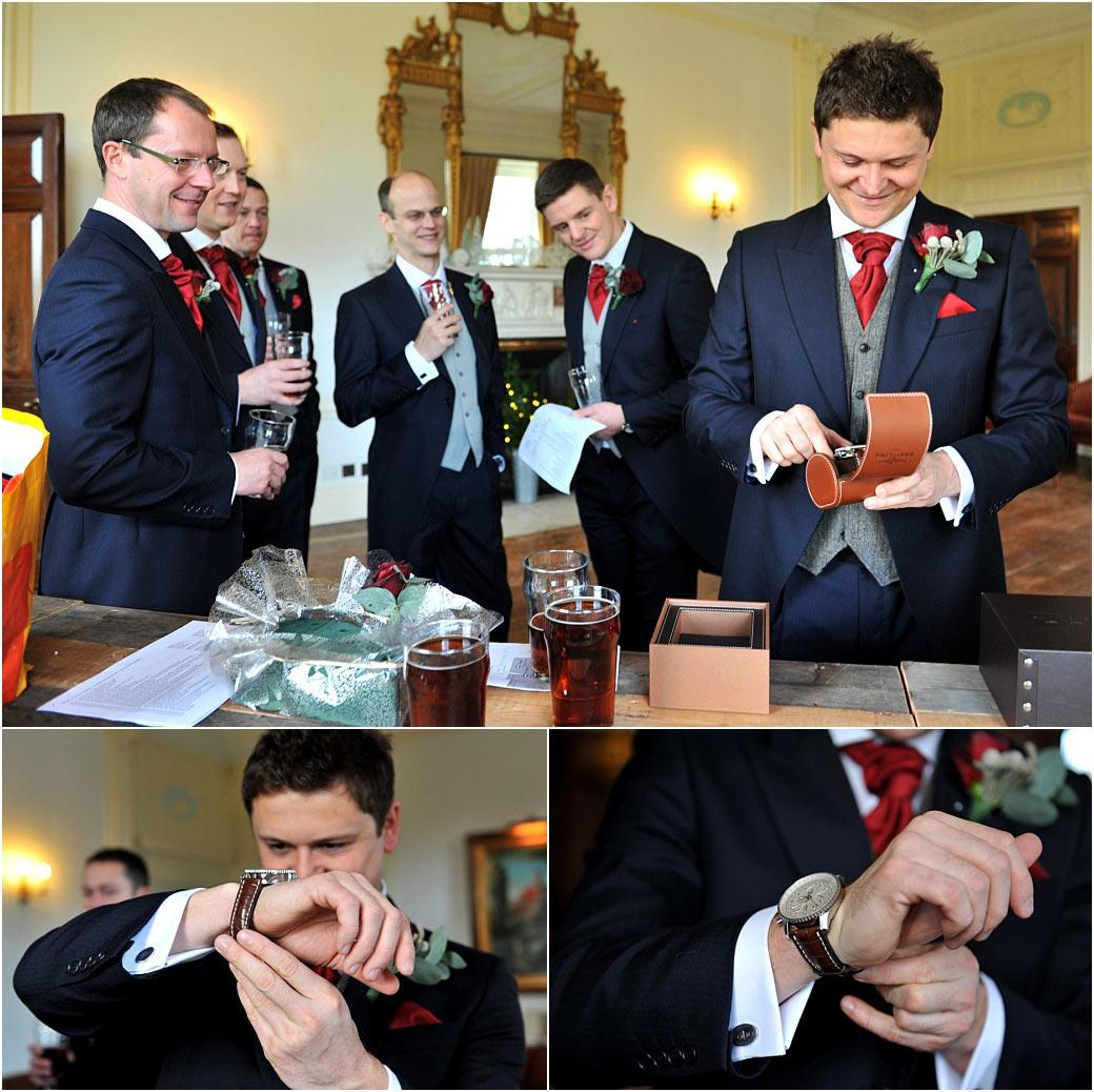 A touched Groom standing with his Groomsmen at Addington Palace in Croydon Surrey opens and puts on a gift of a fabulous watch gift from his wife to be