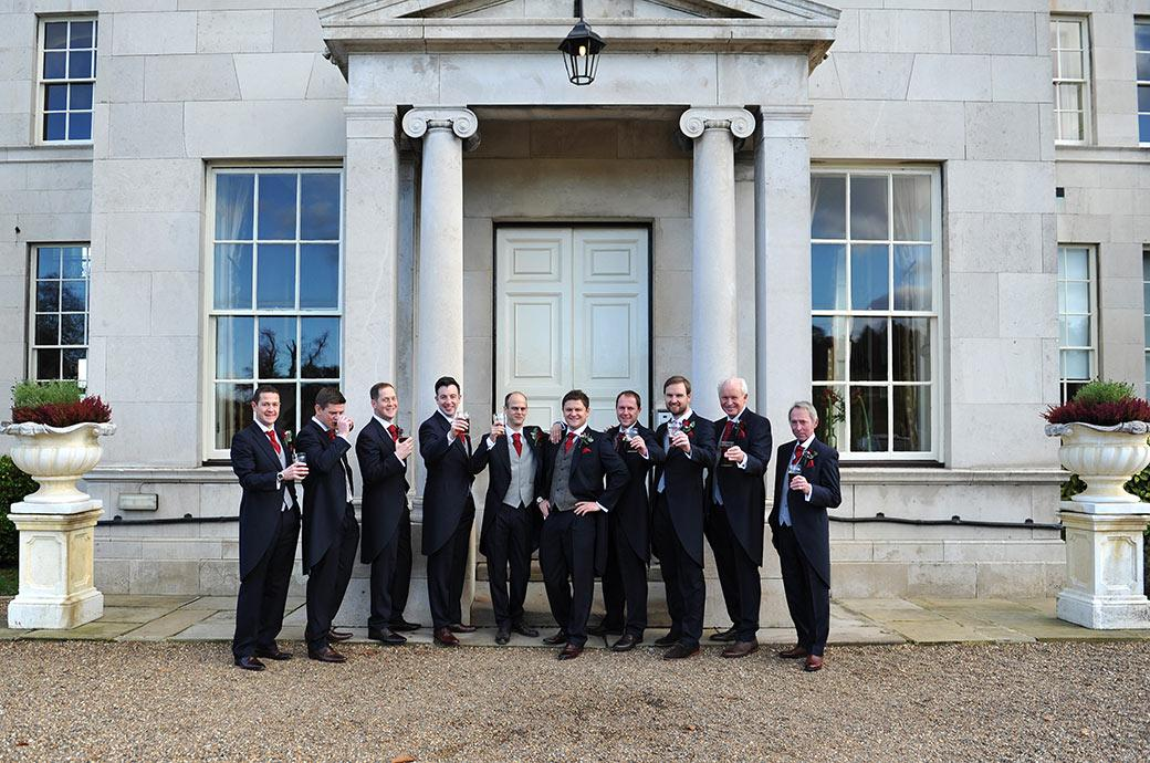 The groom and his groomsmen pose with pints of beer outside the columned front entrance to Addington Palace a wonderfully grand Surrey wedding venue in Croydon