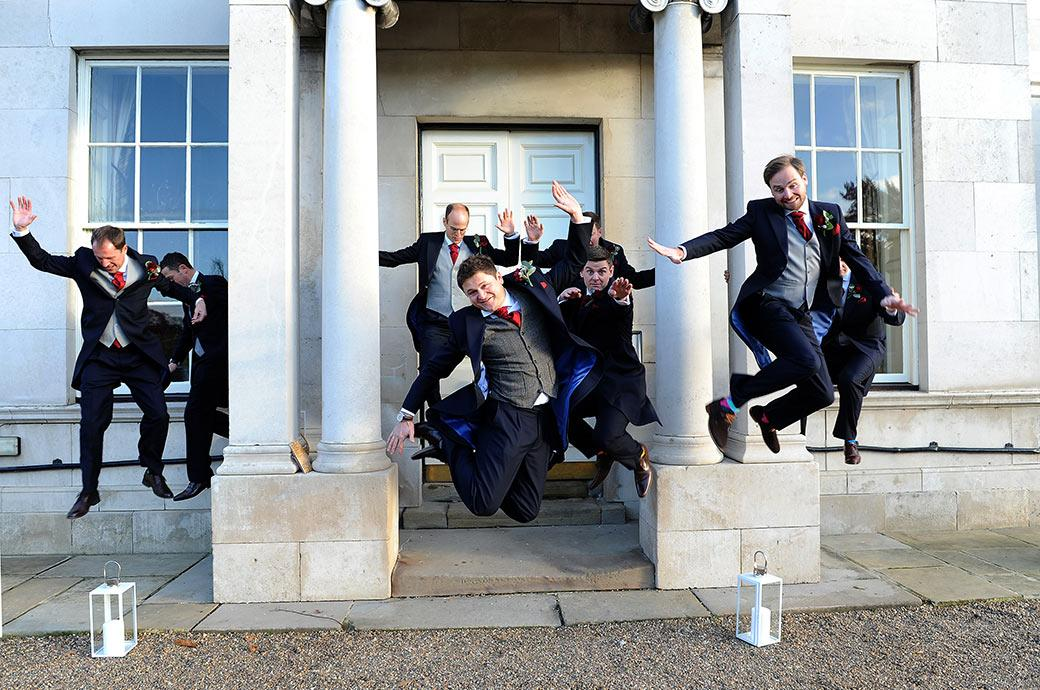 Fabulous wedding photograph of the groom and his groomsmen at the Addington Palace wedding venue in Croydon Surrey jumping off the large columns at the front