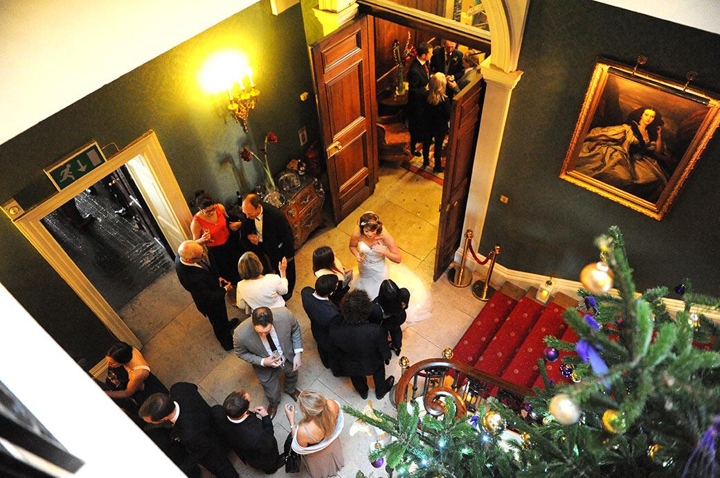 Wedding picture taken at Addington Palace Surrey from the staircase looking down past the large Christmas tree to the Bride below talking to her guests
