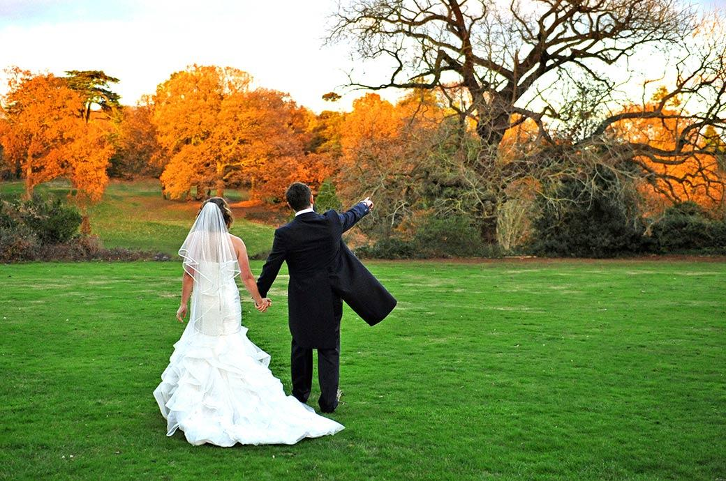 Wedding photograph of the Groom pointing towards the beautiful golden trees as he holds his Bride's hand and walks across the grass at Surrey wedding venue Addington Palace