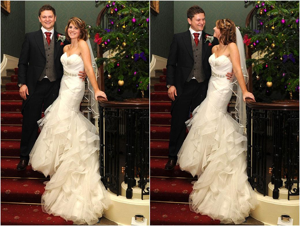 Happy smiling newlywed couple captured in these wedding photos taken at Surrey wedding venue Addington Palace standing on the stairs by a large Christmas Tree
