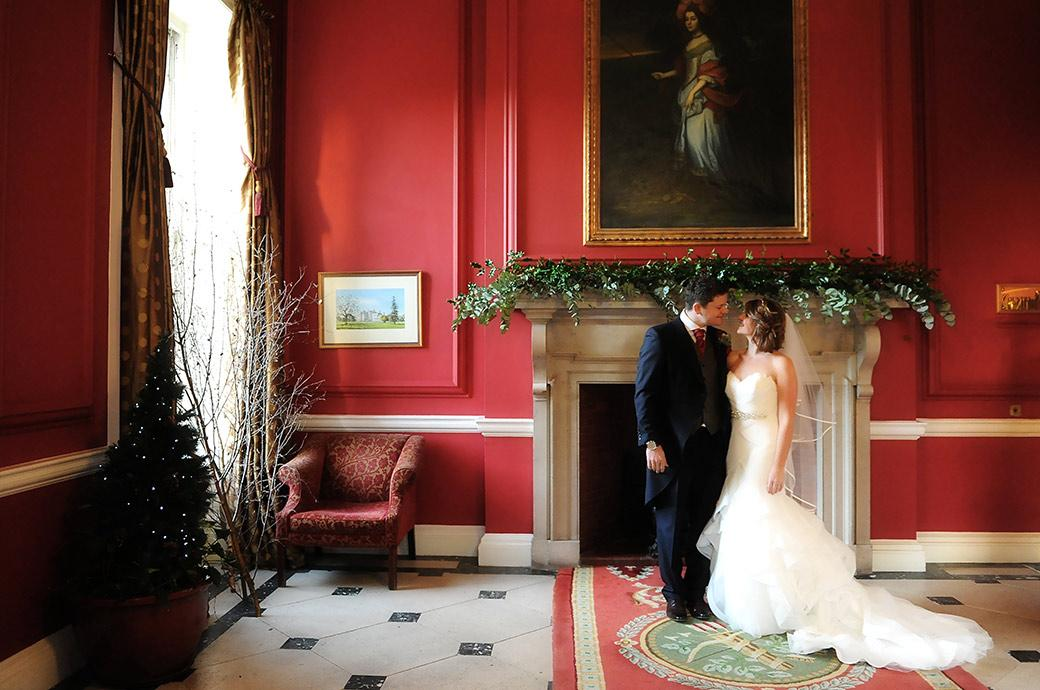 Loving looks between a handsome Bride and groom as they stand in front of a fireplace in the entrance hall to the magnificent Croydon wedding venue Addington Palace Surrey