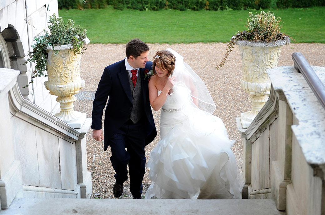 Lovely wedding photo of the Groom hugging Bride in her beautiful wedding dress as they walk up the steps to Surrey wedding venue Addington Palace out of the December cold