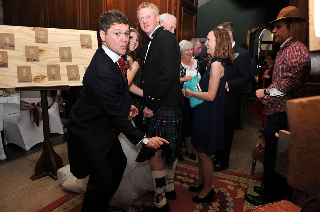 Groom gets naughty in Surrey at the Addington Palace wedding venue as he is caught lifting a guest's kilt whilst talking to the Bride in the receiving line