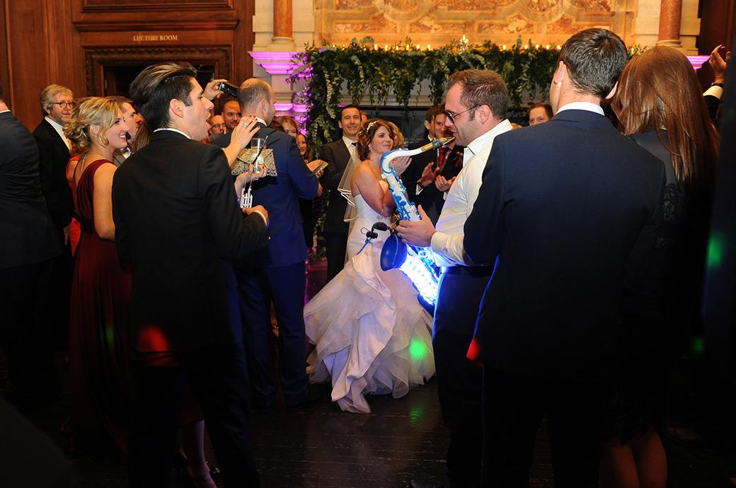 Eye catching wedding picture taken at wedding venue Addington Palace in Croydon Surrey of a saxophonist out in the middle of the Great Hall dancefloor playing his lit up saxophone
