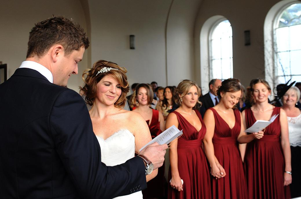 Bride and wedding guests start smiling at the impromptu singing of Christmas is all around me popularised in the film Love Actually in the chapel at Addington Palace Croydon Surrey