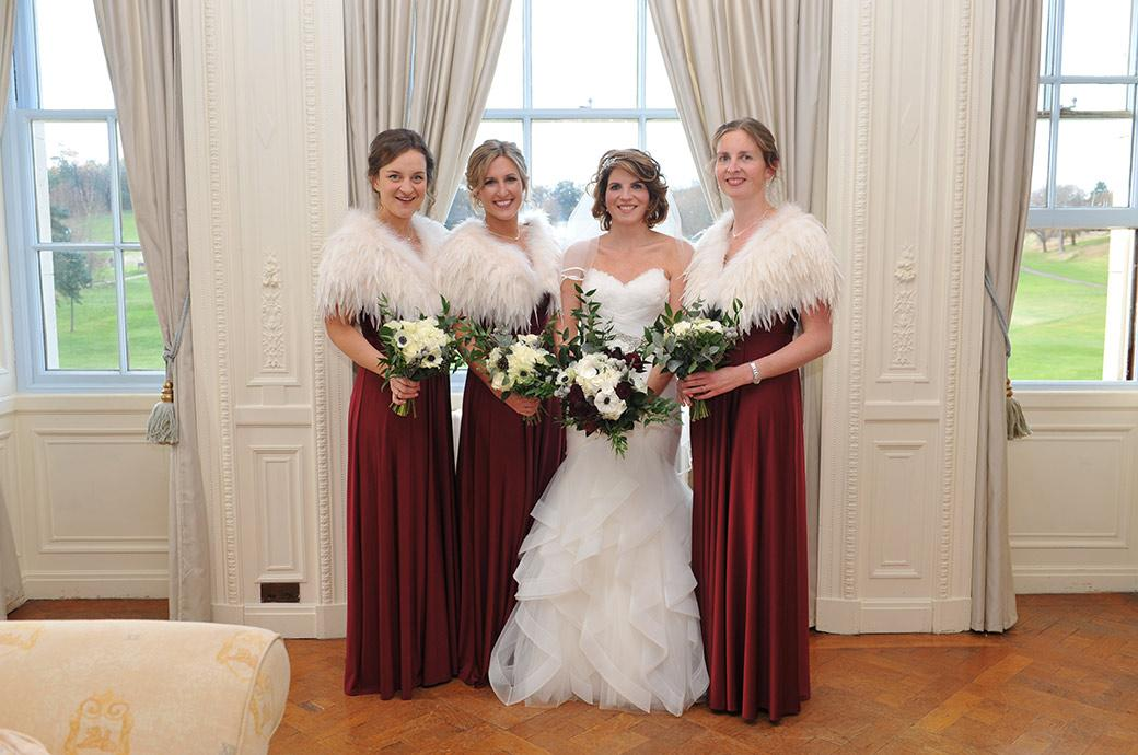 Beautiful Bride in wedding dress topped with feathers and flanked by bridesmaids in white feather stoles at Surrey wedding venue Addington Palace in the Bridal Suite