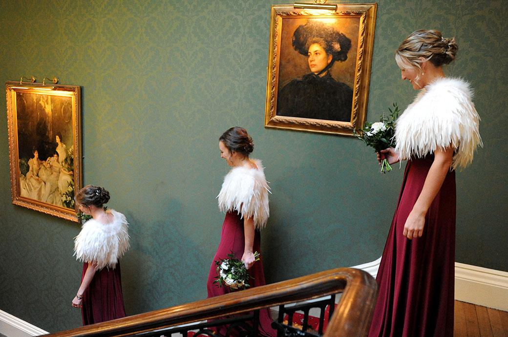 Lovely wedding photo of three elegant bridesmaids in their maroon dresses and white feather stoles descending the stairs on route to the chapel Surrey wedding venue Addington Palace