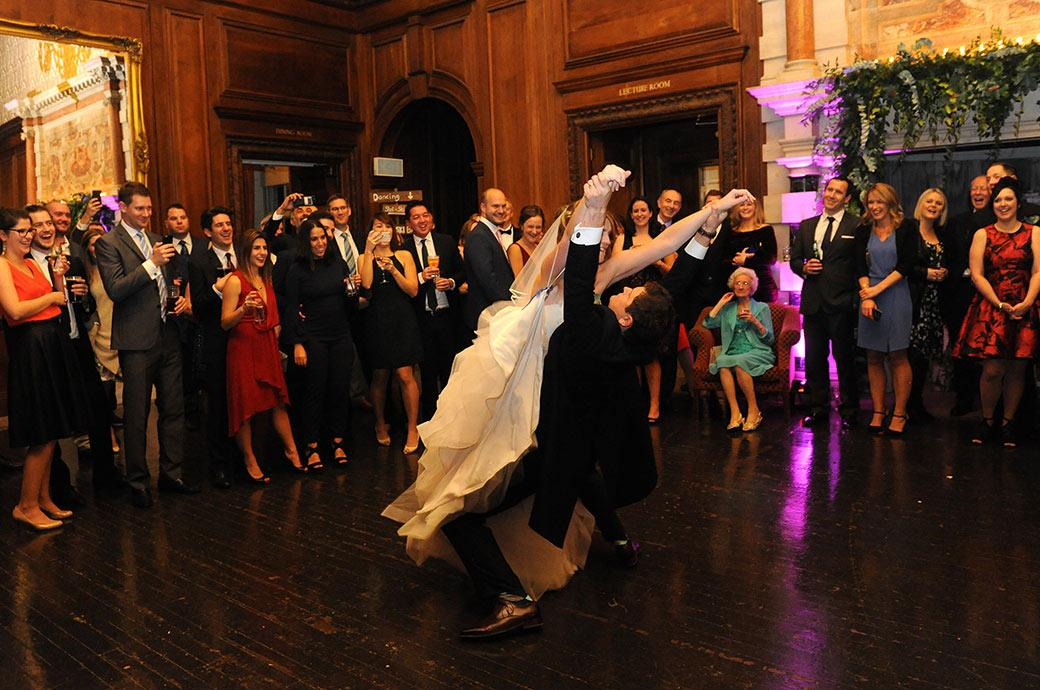 Groom at Surrey venue Addington Palace makes a fabulous dance move lifting up his Bride much to the pleasure of the guests on the dancefloor
