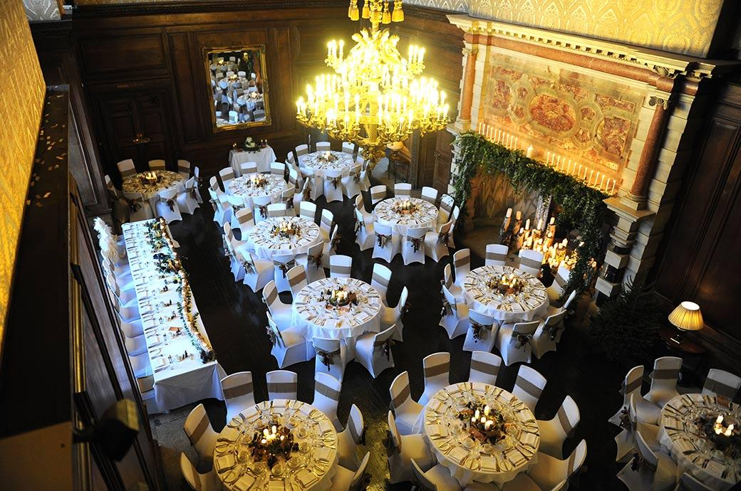 Picture from the gallery at the magnificent Surrey wedding venue Addington Palace of the candle lit banquet set up in The Great Hall for the wedding breakfast