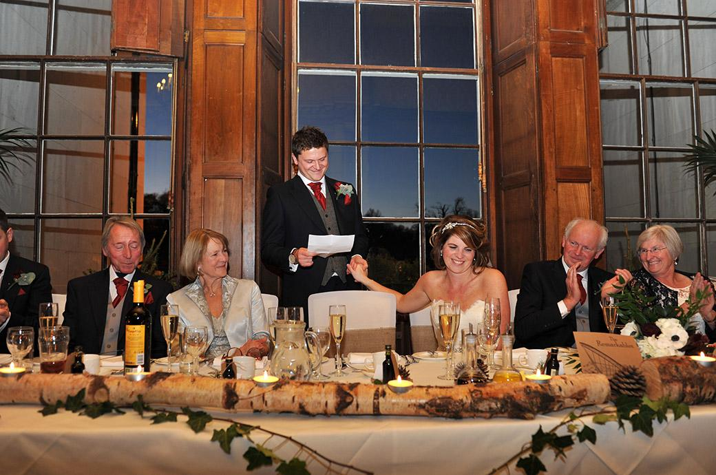 A laughing Bride holds the hand of her smiling groom as he entertains the top table during his very funny wedding speech in the Great Hall at Surrey wedding venue Addington Palace