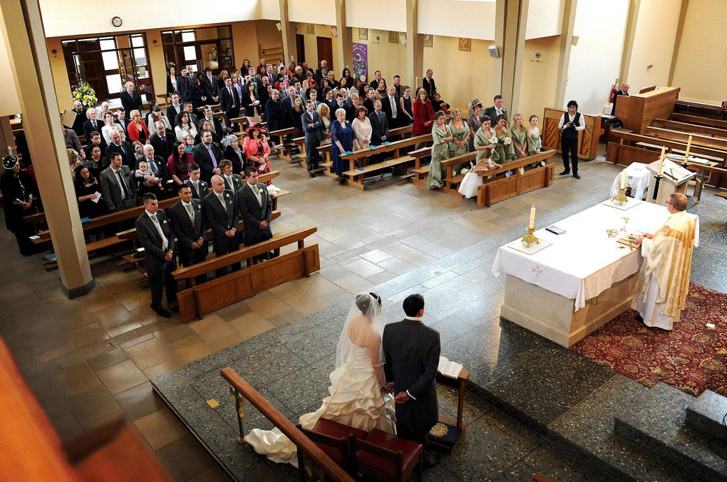An aerial wedding photo taken of the church congregation captured from the front balcony at Addiscombe Catholic Church in Surrey as the Vicar reads the sermon