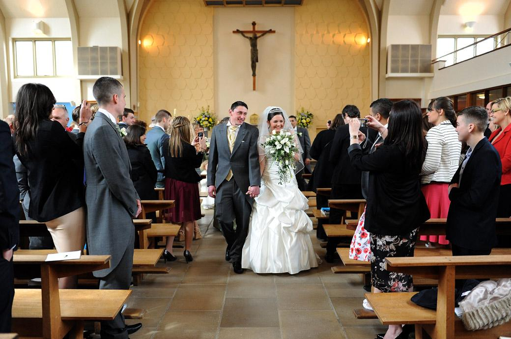 Addiscombe_catholic_church_wedding_couple_walking_down_the_aisle		Bride and Groom smiling at guests as they walk down the aisle Surrey wedding photographer at Addiscombe Catholic Church	119	Bride and Groom smile at their guests as they walk down the aisle in this happy wedding photo taken by Surrey wedding photographers at Addiscombe Catholic Church near Croydon
