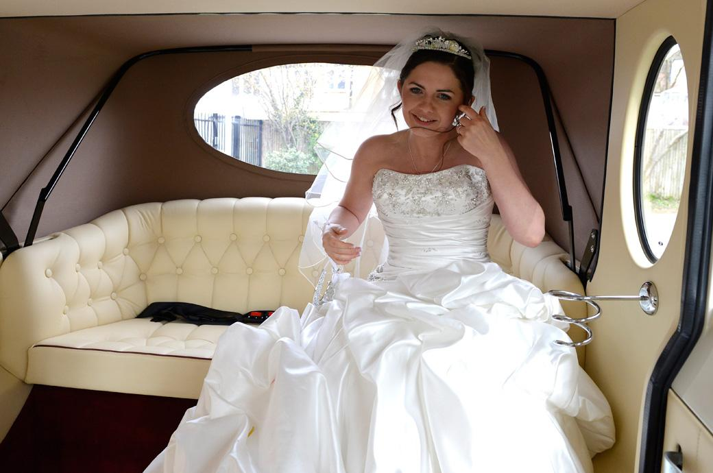 A beautiful and happy Bride adjusts her hair in this lovely fresh wedding photograph taken in the Bridal car outside Addiscombe Catholic Church a Surrey wedding venue