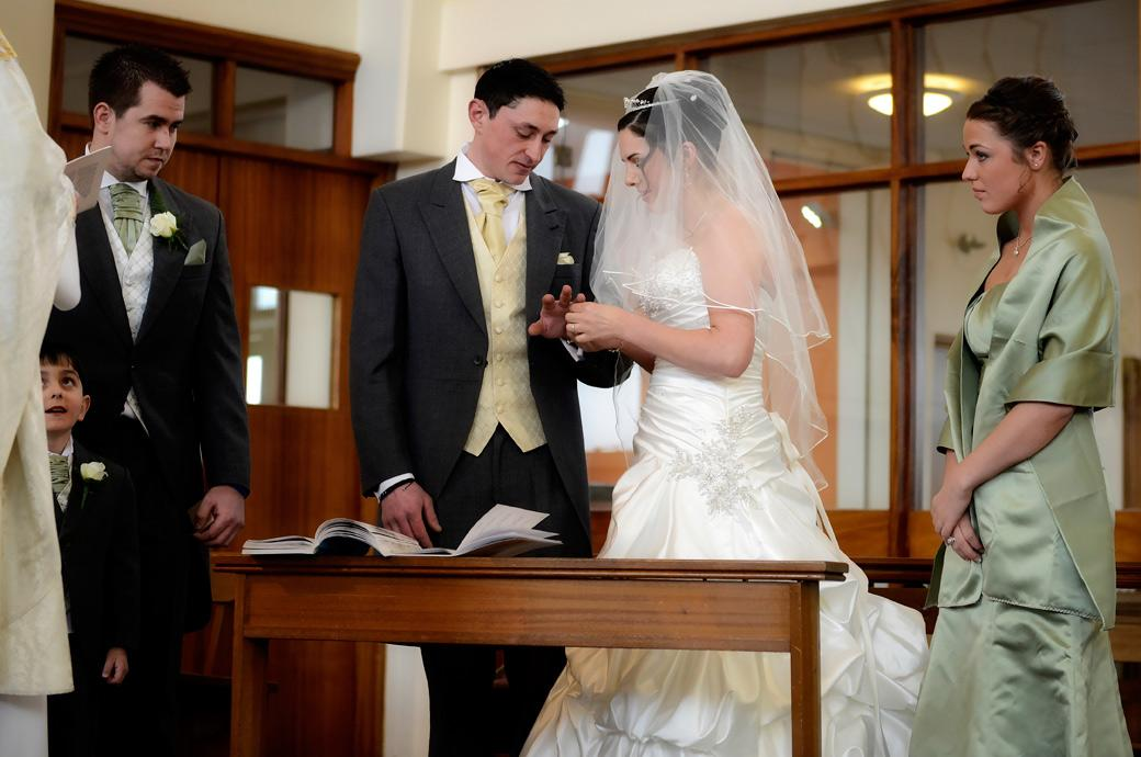 The Bride places the rings on her groom's finger in this tender wedding photograph taken by Surrey wedding photographers at Addiscombe Catholic Church Our Lady of the Annunciation
