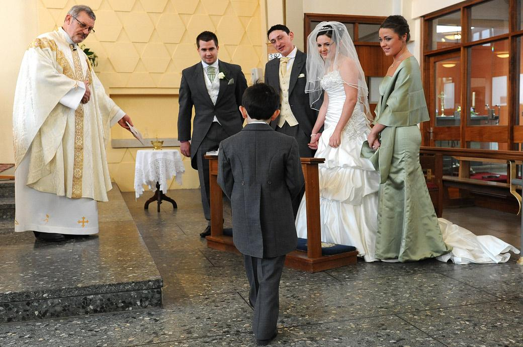 A cute pageboy approaches the vicar with the rings in this sweet wedding picture taken at Addiscombe Catholic Church Our Lady of the Annunciation Surrey wedding venue