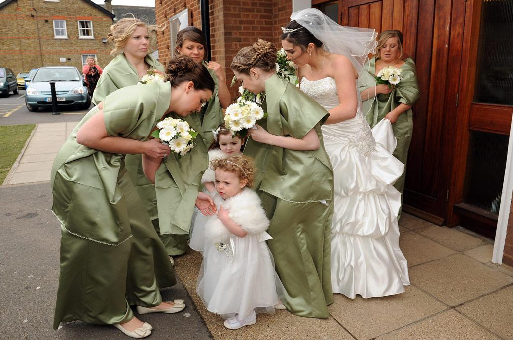 The Bride and Bridesmaids huddling together in this windy wedding photo taken before entering the Addiscombe Catholic Church a modern redbrick Surrey wedding venue