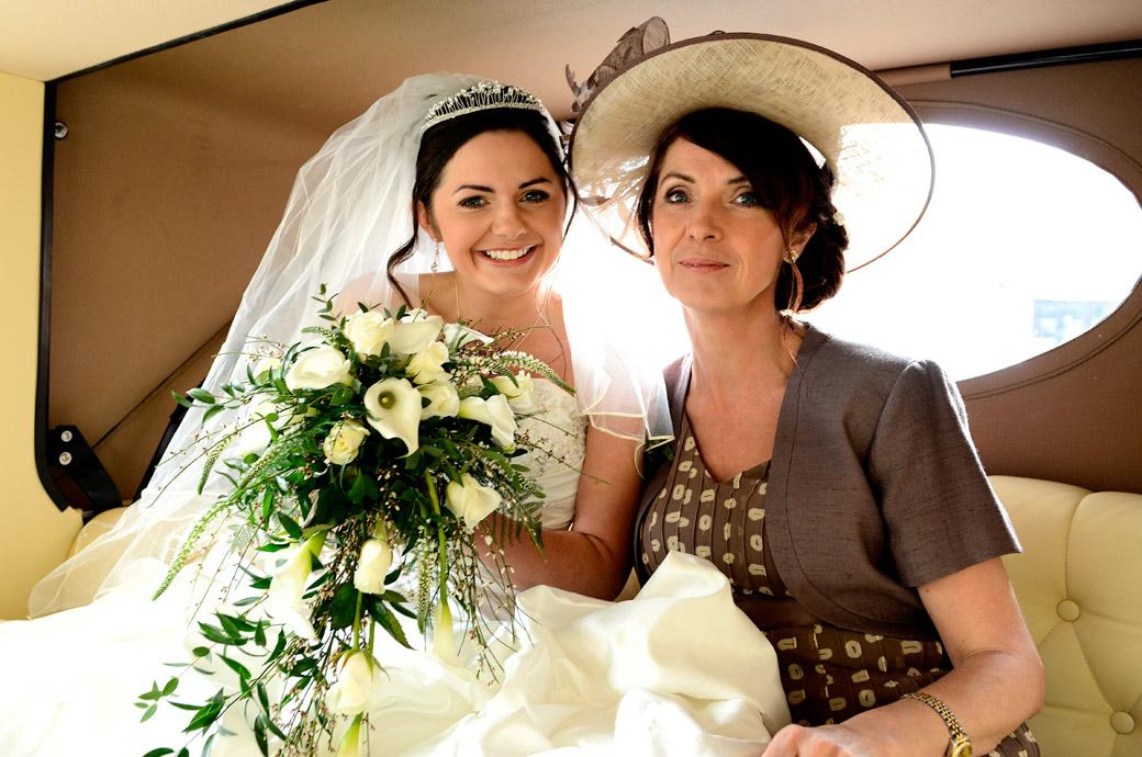 Happy smiling Mother and Bride wedding photograph taken in the wedding car by Surrey Lane wedding photography on the way to Addiscombe Catholic Church near Croydon
