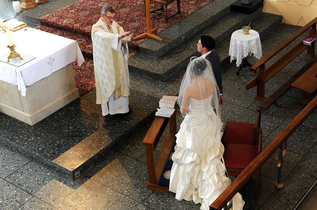 The Vicar blesses the Bride and Groom in this aerial wedding photograph taken from the side balcony at Addiscombe Catholic Church Our Lady of the Annunciation Surrey wedding venue